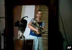 En esta imagen del jueves 4 de abril de 2019, Grettel Montes de Oca Valdés, bailarina profesional y fundadora del grupo Cubanos en Defensa de los Animales, posa con gatos que eran callejeros en su casa de La Habana, Cuba. (AP Foto/Ramón Espinosa)