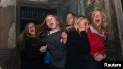 FILE - A group of girls scream in a haunted house in Denver, Colorado, October 2013.