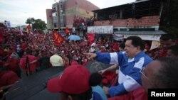 El presidente venezolano y candidato presidencial, Hugo Chávez, saluda a sus partidarios desde un vehículo durante un acto de campaña en San Fernando de Apure el 15 de septiembre de 2012.