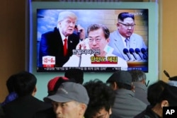 People watch a TV screen showing images of North Korean leader Kim Jong Un, right, South Korean President Moon Jae-in, center, and U.S. President Donald Trump at the Seoul Railway Station