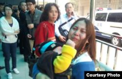 母亲一边抱着小孩一边在哭诉(图片来自新世纪新闻/网民提供)