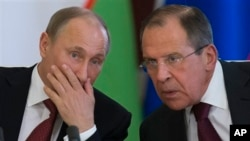 Russian President Vladimir Putin, left, listens to Foreign Minister Sergey Lavrov at Kremlin ceremony, Moscow, April 15, 2013.