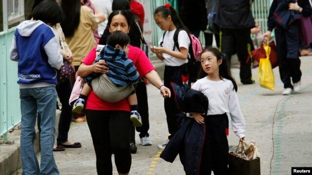Seorang pembantu rumah tangga asing menggendong seorang anak dan menggandeng anak lainnya di luar sebuah sekolah di Hong Kong, 26 February 2013.(REUTERS/Bobby Yip). Seorang PRT Filipina berjuang untuk memperoleh ijin menetap di Hong Kong dengan mengajukan argumentasi ke Mahkamah Agung Tertinngi wilayah itu, Selasa (26/1).