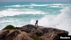 FILE - A man takes photos while standing on a cliff in Bermuda, island shores are battered by winds from an approaching Hurricane. Kate, formerly a tropical storm, has strengthened into the fourth hurricane of the 2015 Atlantic season.