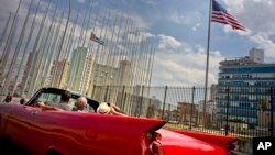 FILE - Tourists ride a vintage American convertible as they drive next to the American flag and a Cuban flag at the United States Embassy in Havana, Cuba, March 18, 2016. AT&T has reached a deal for enhanced roaming and other cellphone services for wireless customers visiting Cuba.