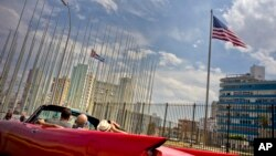 FILE - Tourists ride a vintage American convertible as they drive next to the American flag and a Cuban flag at the United States embassy in Havana, Cuba, March 18, 2016.