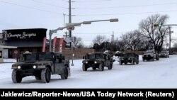 Military vehicles from the Texas Military Department of the Texas National Guard, tasked to transport residents to designated warming centers and other required duties, form a convoy in Abilene, Texas, U.S. February 16, 2021. Greg Jaklewicz/Reporter-News/
