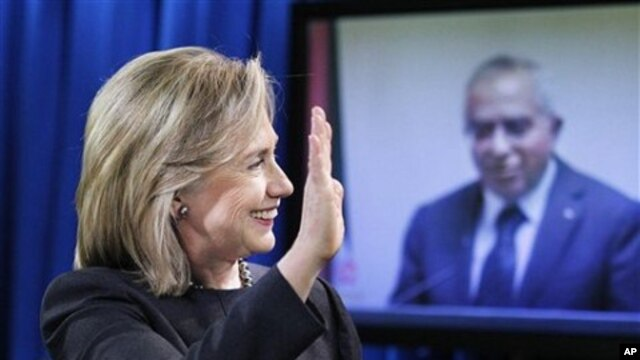 State Secretary Hillary Rodham Clinton waves to Palestinian PM Salam Fayyad, seen on a video monitor, during a video conferencing at the State Department in Washington, announcing the transfer of budget assistance funds to the Palestinian Authority, 10 No
