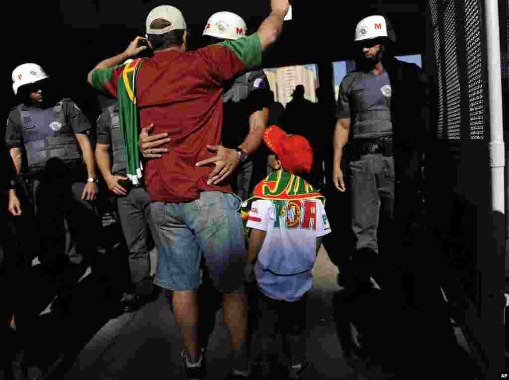 Brazilian police check soccer fans before they go into the stadium to watch Portugal's training session in Campinas, Brazil, June 18, 2014.