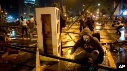 Un manifestante enmascarado se protege de los disparos de la policía en una barricada colocada en el sector de Altamira, en Caracas.