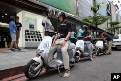 In this Monday, June 15, 2015, photo, Gogoro electric scooters are test driven by potential customers outside a showroom in Taipei, Taiwan.
