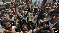 An anti-government protester, center, wearing a gas mask, chants slogans along with others during a demonstration demanding the resignation of Yemeni President Ali Abdullah Saleh, in Sanaa,Yemen, March 21, 2011