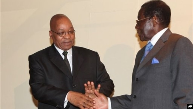 South African President Jacob Zuma and President Robert Mugabe, right, shake hands after discussions in Harare, March 18, 2010.