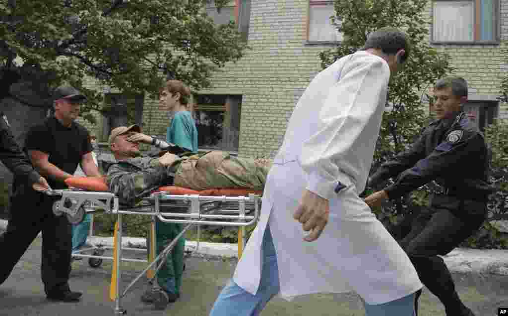 Ukrainian soldiers and a doctor carry a wounded soldier to a hospital in Izyum, near Slovyansk, Ukraine, June 3, 2014.