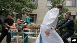 Ukrainian soldiers and a doctor carry a wounded soldier in a hospital in Izyum close to Slovyansk, Ukraine, June 3, 2014.