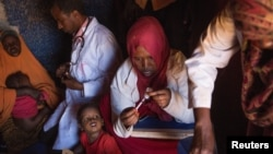 Medical practitioners attend to sick and malnourished children in the drought-stricken Baligubadle village near Hargeisa, the capital city of Somaliland, in this handout picture provided by The International Federation of Red Cross and Red Crescent Societ