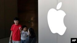 FILE - A Chinese family walks out of an Apple store in Beijing, July 30, 2017.Hundreds of workers protested Wednesday night, Oct. 18, 2017, over bonuses promised through labor brokers who recruited them to work at Jabil Inc.'s Green Point factory, an Apple supplier, in Wuxi city in southern China, according to witnesses.
