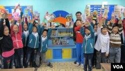Các học sinh chụp hình phía trước của thư viện với nhà từ thiện Nguyễn Quang Thách tại một trường tiểu học trong tỉnh Thái Bình, Việt Nam (M. Brown / VOA)