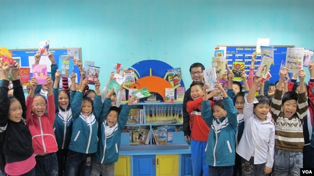 A class poses in front of their library with philanthropist Nguyen Quang, An Bai primary school, Thai Binh province, Vietnam, November 24, 2012. (M. Brown/VOA)
