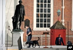 FILE - Law enforcement sweep the area in front of Independence Hall with the statue of President George Washington at left, before the arrival of Pope Francis, Sept. 26, 2015.