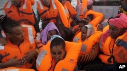 A rescue boat is filled with migrants taken from a vessel in the Mediterranean Sea off the coast of Libya in this Oct. 4, 2016 image taken from video.