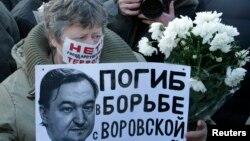 រូបឯកសារ៖ ស្ត្រីម្នាក់កាន់ផ្ទាំងក្រដាសដែលមានរូបរបស់លោកមេធាវី Sergei Magnitsky និងសំណេរដែលសរសេរថា «បានប្រយុទ្ធប្រឆាំងនឹងប្រព័ន្ធចោរកម្ម» ក្នុងអំឡុងពេលធ្វើបាតុកម្មដែលគ្មានការអនុញ្ញាតនៅកណ្តាលទីក្រុងមូស្គូ កាលពីថ្ងៃទី១៥ ខែធ្នូ ឆ្នាំ២០១២។