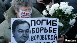 "FILE - A woman holds a placard with a portrait of Sergei Magnitsky during an unauthorized rally in central Moscow, Dec. 15, 2012. The placard reads ""Died fighting a system of thievery."""