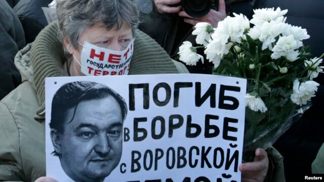"""FILE - A woman holds a placard with a portrait of Sergei Magnitsky during an unauthorized rally in central Moscow, Dec. 15, 2012. The placard reads """"Died fighting a system of thievery."""""""