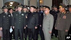 北韩领导人金正日和他的儿子金正恩(中)在平壤接待中国军事代表团(资料照片)