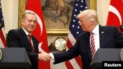 Presiden Turki Recep Tayyip Erdogan (kiri) berjabat tangan dengan Presiden AS Donald Trump pada konferensi pers bersama di Gedung Putih, Selasa (16/5).