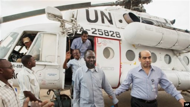 A member of the joint U.N. African Union Mission in Darfur (UNAMID), right, escorts three freed humanitarian workers out of a U.N. helicopter as they landed in El Fasher, North Darfur, Sudan, Saturday, July 19, 2014.