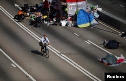 一名男子騎單車穿越示威人士佔領的馬路返回政府總部上班。