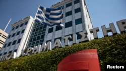 FILE - A Greek flag flutters outside the Athens stock exchange, Greece.