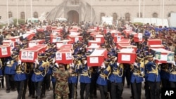 In this handout photo provided by the Defense Ministry, Yemeni officers and soldiers carry coffins of soldiers who were killed in a suicide bomb attack at a parade square in Sanaa, Yemen, May 24, 2012.