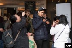 Para pengunjung berbincang menggunakan bahasa isyarat di kafe Starbucks yang pertama mempekerjakan karyawan penyandang tuna rungu atau mengalami kesulitan pendengaran, di Washington DC, 23 Oktober 2018. Para pelayan di kafe tersebut berkomunikasi dengan pelanggan menggunakan bahasa isyarat Amerika.