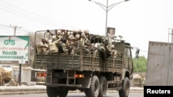 FILE - Soldiers are seen on a truck along a road in Maiduguri in Borno State, Nigeria, May 14, 2015. The Nigerian army reopened a major road Wednesday, linking towns such as Maiduguri and Diffa.