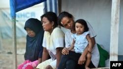 Ibu-ibu dan seorang anak perempuan duduk di depan tenda merea di hunian sementara di Palu, Sulawesi Tengah, 25 September 2019, sebagai ilustrasi. (Foto: AFP)