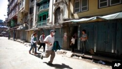 A Nepalese man runs to safety after a second earthquake hit Nepal in Kathmandu, May 12, 2015.
