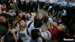 Protesters join hands as they look at fellow protesters being dragged away by the police in Hong Kong's financial Central district after staging an overnight sit-in, July 2, 2014.