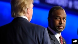FILE - Ben Carson watches as his main rival, real estate mogul Donald Trump, takes the stage during a Republican presidential debate at the University of Colorado, Oct. 28, 2015.