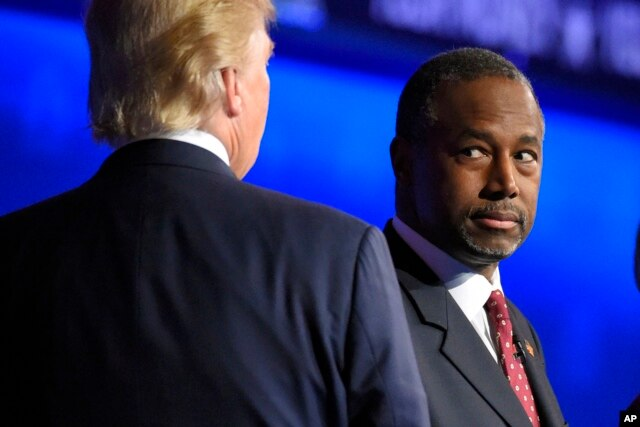 Ben Carson watches as Donald Trump takes the stage during the CNBC Republican presidential debate at the University of Colorado, Oct. 28, 2015.