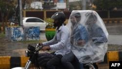 کراچی میں موٹر سائیکل سوار افراد نے بارش سے بچاؤ کے لیے خود کو پلاسٹک بیگ میں چھپایا ہوا ہے۔
