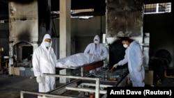 Relawan dari Khan Trust bersiap untuk mengkremasi jenazah seseorang yang meninggal karena COVID-19, di Krematorium Kurukshetra di Surat, India, 11 Mei 2021. (Foto: REUTERS/Amit Dave)