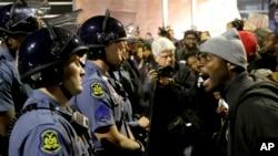 Seorang demonstran membentak seorang polisi di markas besar kepolisian di Ferguson, Missouri (10/10).