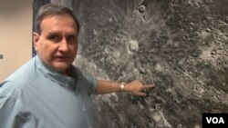 Paul Spudis with a moon mural at the Lunar and Planetary Institute in Houston, Texas. (G. Flakus/VOA)
