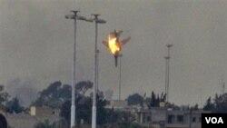 Sebuah pesawat tempur terlihat jatuh tertembak di pinggiran Benghazi, Libya timur, Sabtu (19/3).