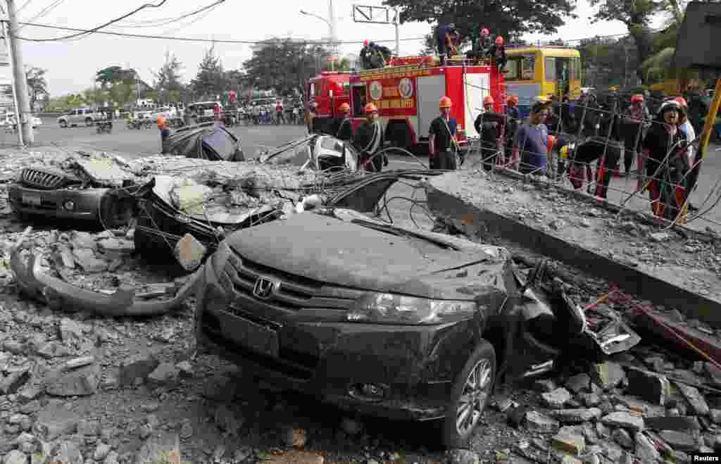 Firefighters stand near damaged vehicles after an earthquake struck Cebu city, in central Philippines, Oct. 15, 2013.