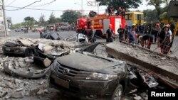 آتش نشانان در نزدیکی یک خودرو که بر اثر زمین لرزه روز سه شنبه در مرکز فیلیپین آسیب دید - ۱۵ اکتبر ۲۰۱۳