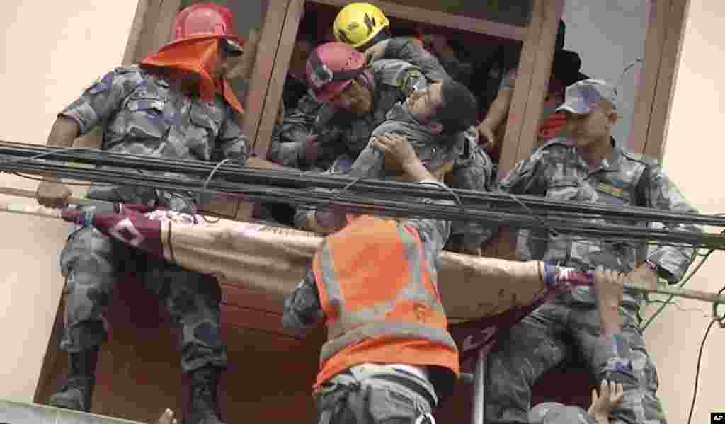 In this image made from video, rescue workers pull a survivor from an earthquake damaged building in Kathmandu, Nepal.