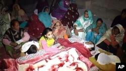 Des Pakistanais pleurent la mort d'un de leur proche, qui a succombé après avoir bu un alcool empoisonné, à Toba Tek Singh, au Pakistan, le 26 décembre 2016.